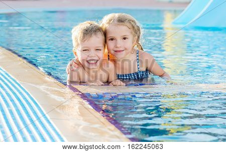 Happy young children in pool hugging at sunset