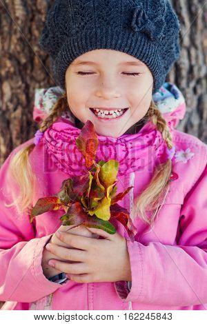 Autumn portrait of a happy little girl outdoors