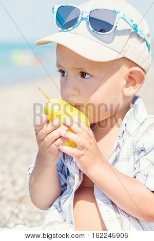 Toddler boy eating a pear in the summer sea