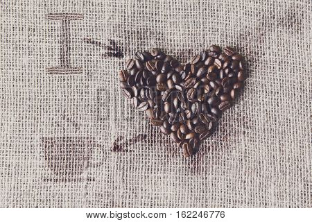 I love coffee. Burlap texture with coffee beans heart shape background, love symbol with cup and arrows. Sack cloth canvas and seeds at hessian textile. Filtered