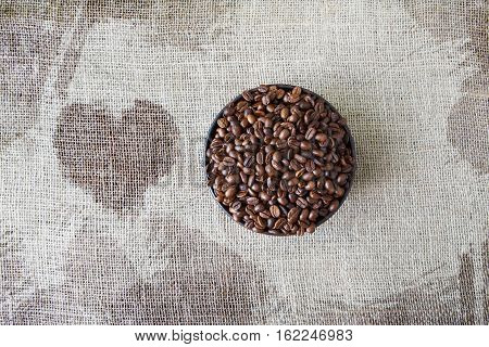 Burlap texture with coffee crop in a bowl background, plenty of robusta beans in plate with heart shape spot near. Sack cloth canvas with copy space. Heap of seeds at hessian textile