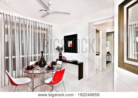 Colorful and classic dining room interior of a modern house with floor tiles there is a round glass table holding a shiny black vase surrounded by black mugs and Saucer chairs has a nicely shaped surface near the window