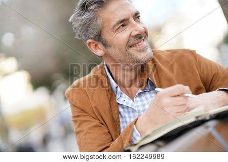 Businessman sitting on public bench, working with agenda
