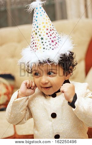 Happy south asian boy wearing birthday hat and celebrating his birthday.