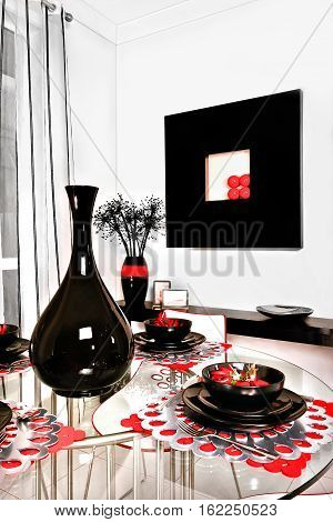 There is a shiny black vase surrounded by black mugs and dishes probably made from ceramic. There are beautiful red color decorations around dishes there is a small black table or shelf fixed to the white wall
