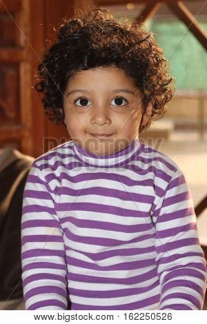 cute curly hair light skin south asian boy smiling wearing white lining shirt