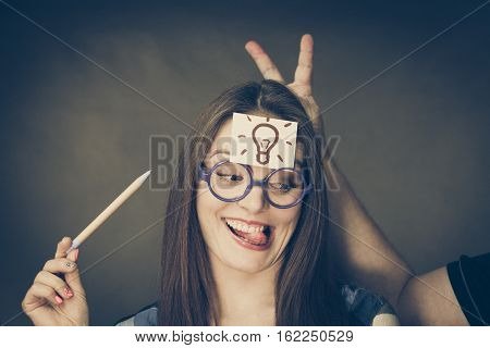 Woman confused thinking seeks solution paper card with light idea bulb on her head. Eureka creativity concept. Male hand with funny gesture behind her head