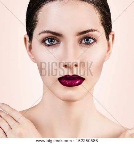 Young beautiful woman with healty fresh skin and bright make-up over beige background. Spa concept.