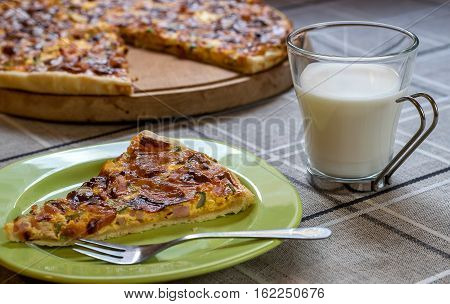 Homemade quiche (tart) with pickles, ham, prosciutto and cheese