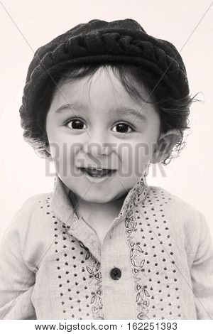 Portrait. happy little south asian boy wearing cultural dress and hat. smiling and looking in the camera.