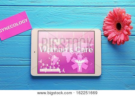 Tablet computer, card and gerbera flower on wooden background. Gynecology concept