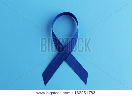 Blue ribbon on color background. Colon cancer concept