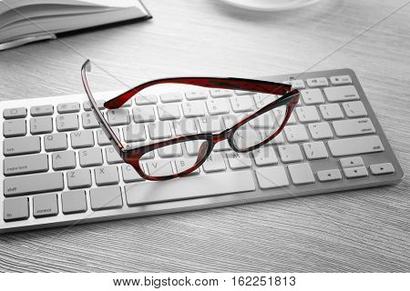 Glasses and keyboard on wooden table. Healthy eyes concept
