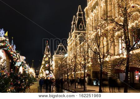 Christmas Fair. Decorated Christmas tree. Bright lights garlands. The festive mood. Red and gold balloons ribbons and flowers. Fair on the Red Square. GUM