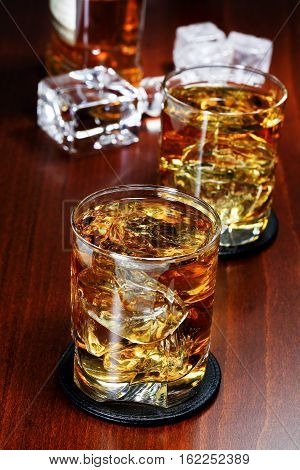 two glasses of whiskey with ice on wooden surface