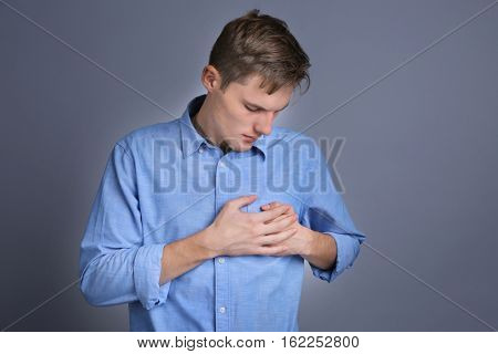 Young man holding hands on heart against color background