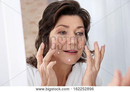 Senior woman applying cream on face in front of mirror, closeup