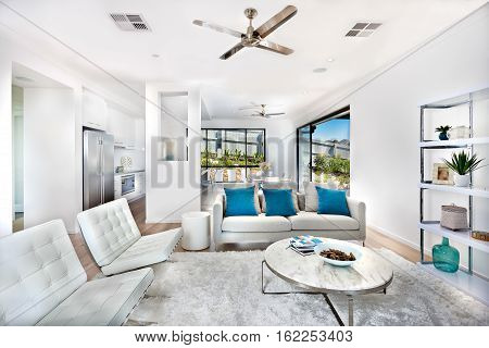 Total white living room decoration interior with the kitchen of a luxury house expressing the color of white within same color walls and furniture. There are round tables and sofas with pillows on the wool carpet next to the shelf.