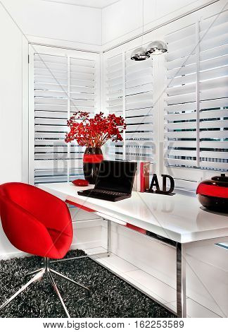 This modern workroom of a luxury house has a red chair and a small white table on the wool carpet floor. Room walls and windows are white. A silver table lamp over the table that included a laptop and a black vase with flowers
