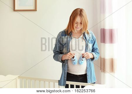 Pregnant woman holding baby bootees on belly