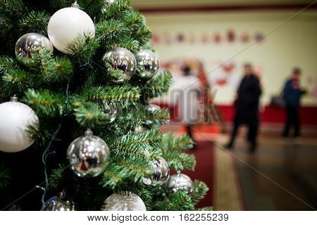 New Year fir with balls and garlands in mall