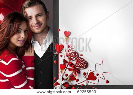 Happy couple posing with Valentine's day decoration with white copy space