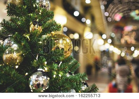 Decorated Christmas tree on blurred background of shop, photo toned
