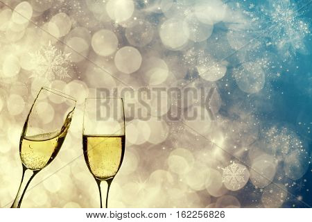 Glasses with champagne against fireworks and holiday lights - New Year background