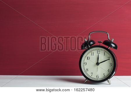 Still life Retro black clock on white table and red grunge background.