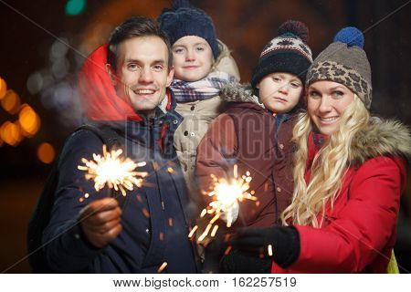 Parents with kids with Bengal lights in park at night in new year