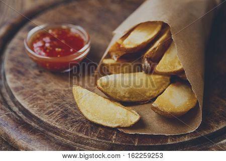 Potato wedges wrapped in brown craft paper. Fast food take away on rustic wood. Fried slices with tomato sauce. Filtered