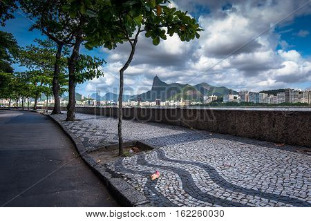 Sidewalk of Urca Neighborhood and View of Rio de Janeiro in the Horizon With Clouds in the Sky