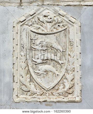 Ancient noble emblem with three dolphins (or fish) with cross on a wall in Venice
