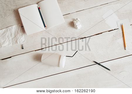 Workplace of untidy students flat lay, free space. Top view on blank copybook, pencils, coffee-to-go cup and paper wads scattered on white wooden table. Mess, disorder, bad form concept