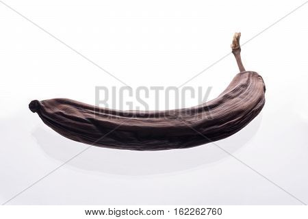 Spoiled brown banana lying on white background