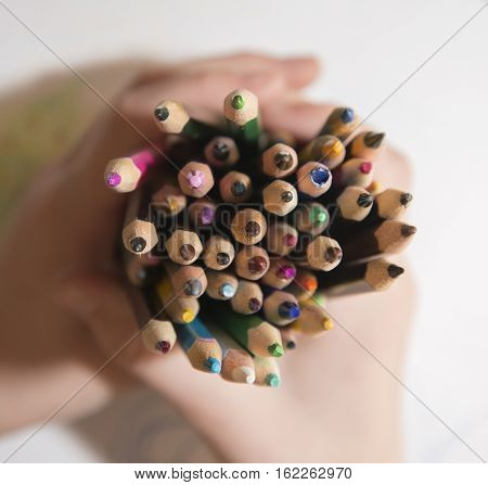 Child Holding A Stack Of Pencils.