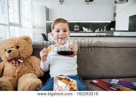 Photo of cute boy sitting on sofa with teddy bear at home and watching TV while eating chips. Holding remote control.