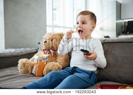 Little happy boy sitting on sofa with teddy bear at home and watching TV while eating chips. Holding remote control.