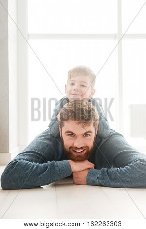 Photo of little cheerful boy lies on the floor with his bearded father while look at the camera.