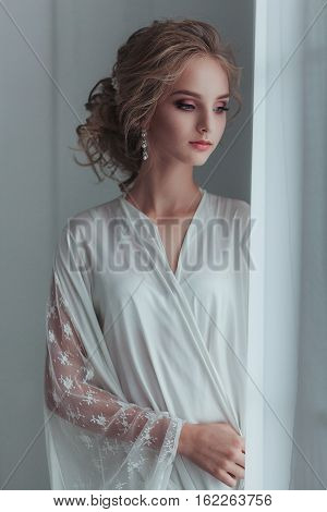 Morning of the bride. Beautiful young woman in elegant white robe with fashion wedding hairstyle standing near the window.