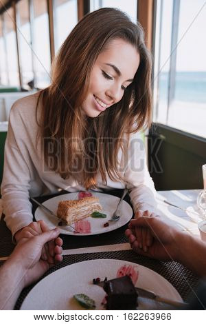 Vertical image of shy woman sitting by the table with food on date in cafe near the sea. First-person view