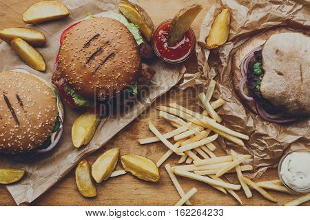 Fast food dish top view. Meat burger in craft paper, potato chips and wedges. Take away composition. French fries, hamburger, mayonnaise and ketchup sauces on wood. Menu or recipe background