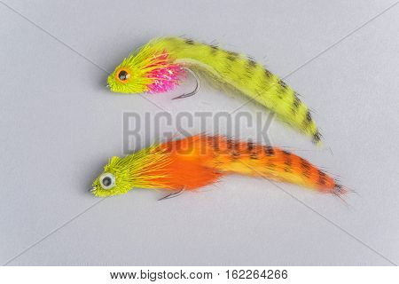 Close Up of Two Colorful Fly Fishing Flies on Gray Background