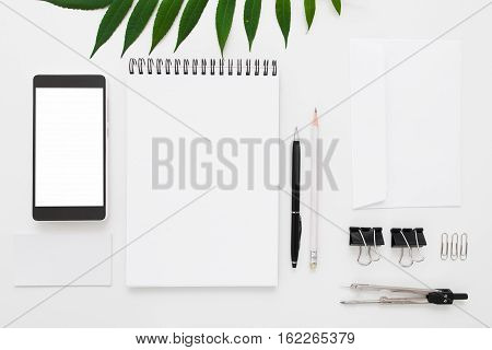 Black and white stationery with green leaves flat lay. Top view on Smartphone with blank screen and empty notepad with writing instruments. Art, business, creation, imagination, education concept