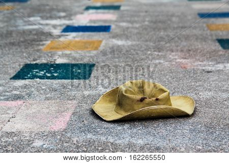 Old, worn scout hat is on the concrete floor