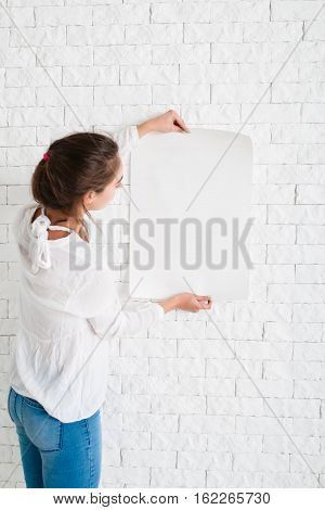 Young woman looking at empty sheet of paper, mockup. Female holding blank poster and reading information on it, copy space for text or advertisement. Promo, warning message concept