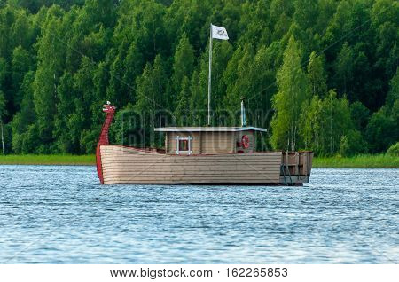 Valdaysky District, Russia - June 16, 2013: Modern wooden boat, stylized like viking ship with a dragons head for the entertainment of tourists by Andrey Kopylov, aka linkpusher