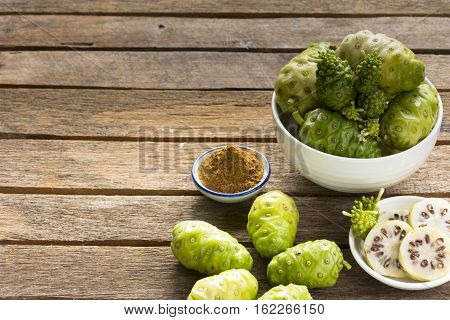 Noni fruits and noni slice with noni powder on old wooden background.Zoom in.