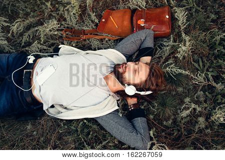 Napping at nature young man top view. Bearded guy in headphones listen to music, sleeping on green grass, free space. Leisure, hobby, relax concept