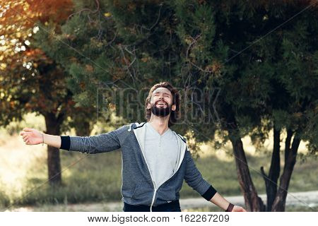 Smiling man enjoying wind blowing in forest. Happy man feeling joy while walking at nature, free space on green trees background. Life love, joy, fresh air, renovation concept